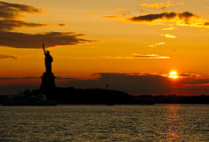 Statue of Liberty against sunset - saturated silhouette. Shot from the ferry to Staten Island Royalty Free Stock Photos
