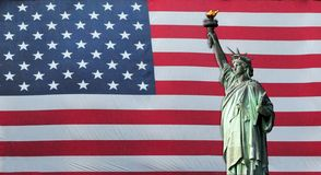 Statue of Liberty with American Flag. In the background Royalty Free Stock Image