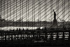 Statue of Liberty as seen through Brooklyn Bridge. Silhouette of Brooklyn Bridge and Statue of Liberty in black and white royalty free stock images