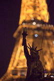 Statue of Liberty on the background of the evening Eiffel Tower royalty free stock image
