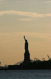 Statue of Liberty in blush color sky. Scenic view of the Statue of Liberty in a blush color evening New York skyline Stock Images