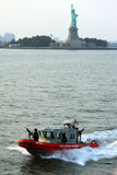 Statue of Liberty and boat. A Coast Guard boat in the water near the Statue of Liberty Royalty Free Stock Image
