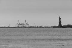 Statue of Liberty with cranes on background. Black white picture with the statue of liberty and the harbor in the background Royalty Free Stock Photography
