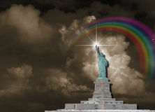 Statue Of liberty. With dark sky and rainbow Stock Photos