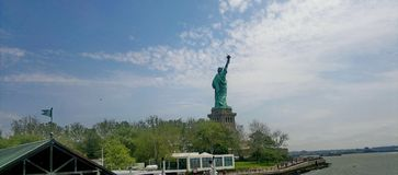 Statue of liberty in the distance. A picture of part of the stanton island in new york city and the statue of liberty in the distance,in a summer day of june Royalty Free Stock Images