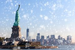 The Statue of Liberty free of tourists and New York City Downtown on sunny early morning during snowfall. stock photography