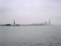 Statue of Liberty and Jersey City on a cloudy day. View from the Staten Island Ferry Stock Images