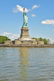 Statue of Liberty on Liberty Island with full reflection. On water on a sunny day with clear blue sky Stock Photo