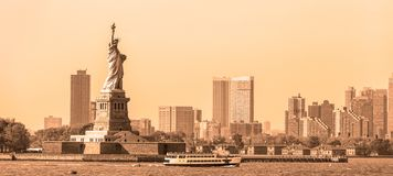 Statue of Liberty with Liberty State Park and Jersey City skyscrapers in background, USA. Black and white yellow toned image stock photography