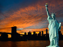 Statue of Liberty and Manhattan at sunset. Stock Image