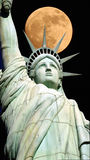Statue of Liberty and moon. The Statue of Liberty with the moon in the background stock photo