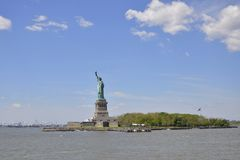 Statue of Liberty, New York City. The Statue of Liberty in a clear blue sky with some white clouds; Liberty Island royalty free stock photography