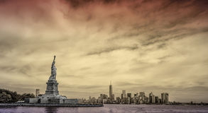 Statue of Liberty with New York City skyline in background. The Statue of Liberty and Ellis Island in foreground with New York City in a sunset background Stock Photography