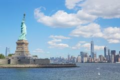 Statue of Liberty and New York city skyline, blue sky. Statue of Liberty and New York city skyline in a sunny day, blue sky and approaching white clouds Stock Image