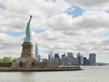 The Statue of Liberty and New York City Skyline. With cloudy sky background Stock Photos