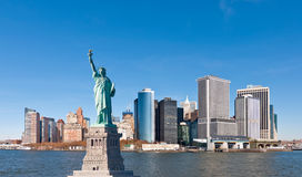 The Statue of Liberty and New York City Skyline. A vantage point in New York Harbor, the iconic island of Manhattan lies just ahead. An eclectic mix of buildings Stock Image