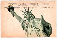 Statue of Liberty in New York, collage on sepia vintage postcard background, word postcard in several languages stock photography