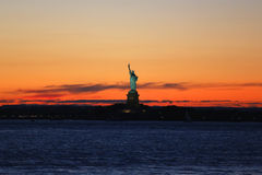 The Statue of Liberty in New York Harbor at sunset Royalty Free Stock Images