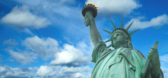 Statue of Liberty panorama with bright blue cloudy sky, New York. New York royalty free stock images