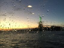 The Statue of Liberty in the rain behind the glass. The view of the Statue of Liberty behind the glass of the Staten Island Ferry. Shot under the rain, in the Royalty Free Stock Images
