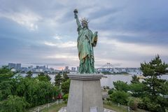 Statue of Liberty and Rainbow bridge in Odaiba at sunset Royalty Free Stock Photography