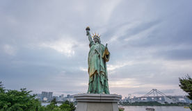 Statue of Liberty and Rainbow bridge in Odaiba at sunset Stock Image