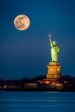 Statue of Liberty and a rising supermoon. In New York City royalty free stock photos