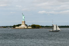 The Statue of Liberty with the sailing shipin New York. Stock Image