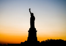 The Statue of Liberty silhouette against crimson sunset Royalty Free Stock Photos
