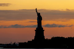 Statue of Liberty silhouette against crimson sunset. Shot from the ferry to Staten Island Royalty Free Stock Photo