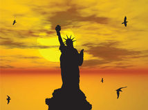 Statue of Liberty Silhouette against the Sunset Il. The silhouette of the Statue of Liberty accompanied by flying seagulls with the setting sun in the distant Royalty Free Stock Photo