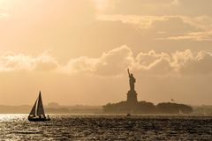 Statue of Liberty at Sunset. On New York Harbor along with it's sailboats Royalty Free Stock Images