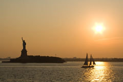 Statue of Liberty at sunset. Ellis Island with statue of liberty and a sailing boat in the evening glow at sunset. New York city Royalty Free Stock Photography