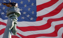 Statue of liberty torch & flag. The torch of the Statue of Liberty with an American flag as a background royalty free stock photo