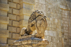 Statue of a lion holding the shield with the coats of arms near. Statue of lion holding shield with the coats of arms of Antonio de Vilhena near Mdina Main Gate Royalty Free Stock Image