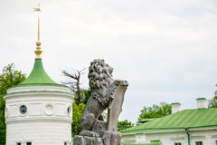 Statue of lion holding a shield in its paws. Regal lion leaning on empty heraldic shield near the castle entrance. The palace and Stock Image