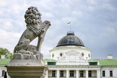 Statue of lion holding a shield in its paws. Regal lion leaning on empty heraldic shield near the castle entrance. The palace and Stock Images