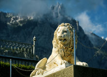 Statue of lion at the Vorontsov Palace on the background of Ai-Petri mountain, Crimea. ALUPKA, RUSSIA - MAY 20, 2016: Statue of lion at the Vorontsov Palace on stock photos