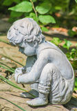 Statue. Of little boy stooping Stock Photo