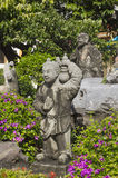 Statue of little Chinese girl with a monk in green garden. Stock Image