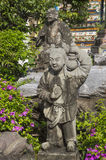 Statue of little Chinese girl with a monk in green garden in Ban. Asian figurines in green garden Stock Photos