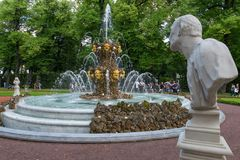 The statue looks at the fountain. SAINT PETERSBURG, RUSSIA - AUGUST 18, 2017:  Fountain Crown in the Summer garden. This park is one of the oldest in Saint Royalty Free Stock Photography