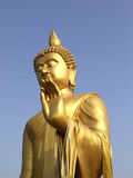 Golden statue of Lord Buddha raising left hand royalty free stock photography