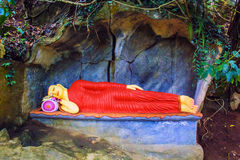 Statue of a lying sleeping Buddha in a stone cave in Sri Lanka Stock Photos
