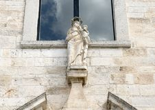 Statue Maddon and Child on the facade of the church of Santa Maria della Stella, Ostunia. Pictured is a closeup view of a statue of Maddona and Child.  The Royalty Free Stock Image