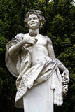 Statue of a man carrying a wine goblet and a grape Stock Images