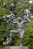 Statue of Man chasing four geniuses, Vigeland park Stock Photo