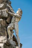 Statue of a man climbing a rock. Useful for concepts royalty free stock image