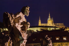 The statue of a man with a hammer looks at the temple of St. Vitus. Prague. Stock Photo