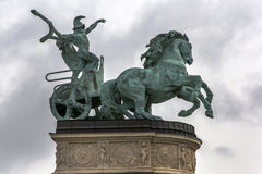 The statue of a man holding a snake driving his horse drawn chariot a symbol of war in Hero`s Square in Budapest in Hungary. The statue of a man holding a snake Stock Photo
